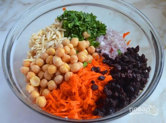 6.В миску сложите консервированный нут, морковь, сушеную смородину, измельченную зелень, лук, чеснок.