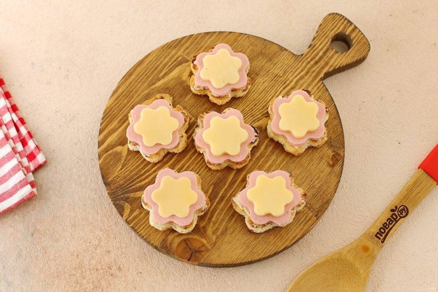 Сверху выложите колбасу и накройте ее сыром. Детские бутерброды готовы.