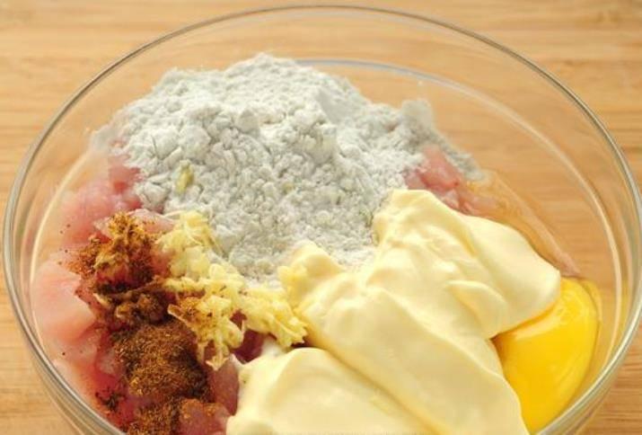 Смешайте в миске куриное филе, майонез, крахмал, яйцо, чеснок, соль, специи и хорошо перемешайте.