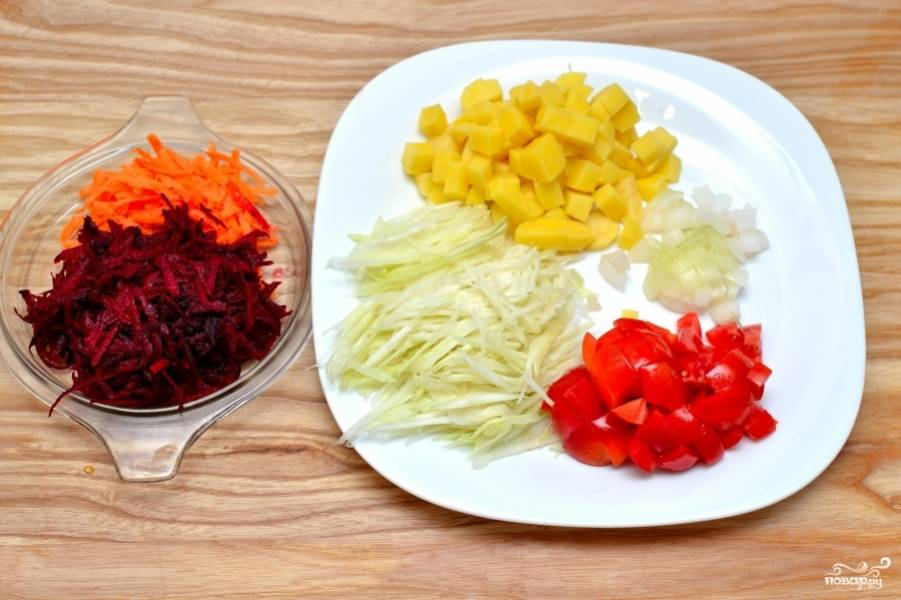 Помойте все овощи. Морковь и свеклу натрите на крупной тёрке. Капусту нашинкуйте. Помидоры, картофель и репчатый лук нарежьте маленькими кубиками.