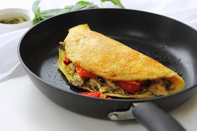 8. Аккуратно свернуть так, чтобы начинка оказалась внутри. Жарить омлет с курицей и помидорами в домашних условиях до готовности.