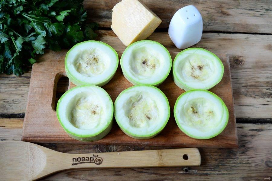 Кабачок порежьте на кружочки толщиной 1 см. В каждом кружочке ложкой выньте немного мякоти, чтобы получилось небольшое углубление. Делайте это аккуратно, чтобы не проткнуть кружочек полностью, иначе будет вытекать сок из помидора. Внутри кабачок присолите и поперчите по вкусу.