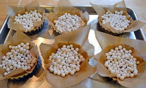 8. Чтобы тарталетка не деформировалась в процессе выпечки в середину вложить небольшой кусочек пергамента и насыпать горох или фасоль. Также можно вложить еще одну формочку.