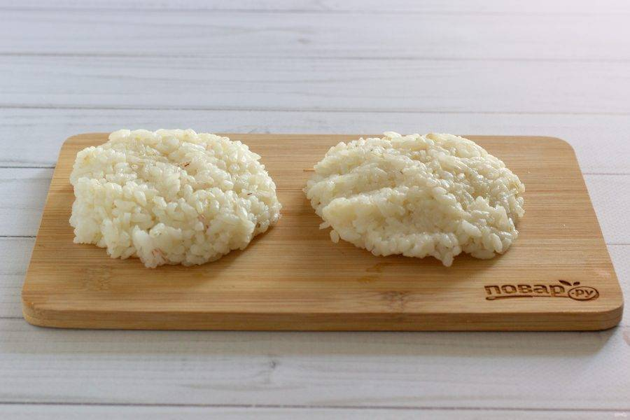 В рис добавьте крахмал, тщательно перемешайте. Если рис недостаточно соленый, то посолите по вкусу. Для наглядности фото сделаны на досочке, но делать будем всё в ладонях. Ладони обязательно смочите водой. Столовой ложкой возьмите рис и выложите на ладонь. Расплющьте его в лепешечку.