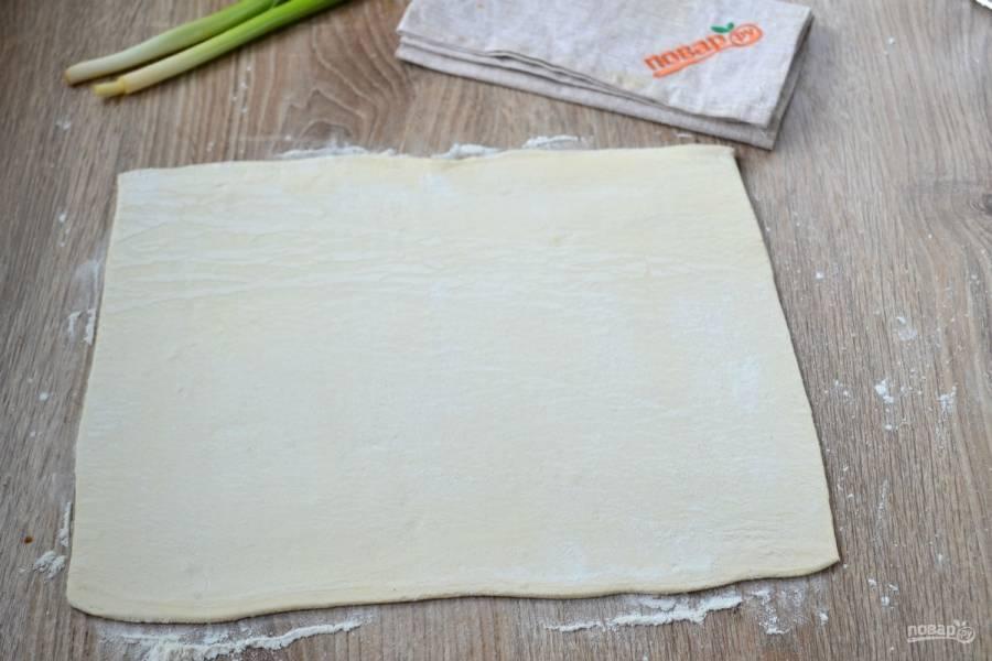 Лист слоеного теста слегка разморозьте, чтобы его можно было раскатать. Выложите его на рабочую поверхность, присыпанную мукой и раскатайте в тонкий пласт (толщина около 2-3 мм).