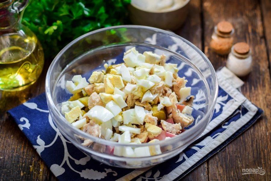 Куриные яйца отварите и почистите, нарежьте кубиками и добавьте в салат.