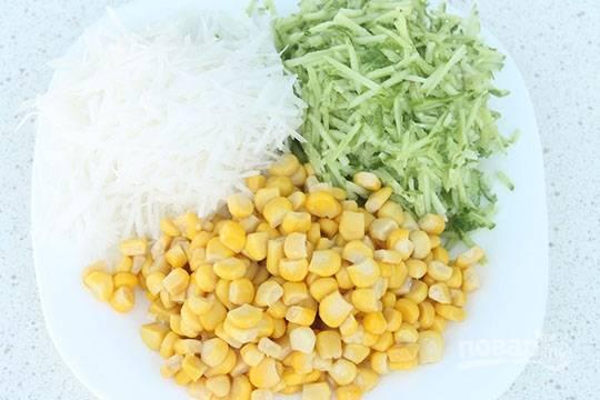 Редьку и огурец помойте, почистите и натрите на тёрке для корейской моркови. Отожмите овощи от сока. Соедините их с кукурузой без жидкости из банки.