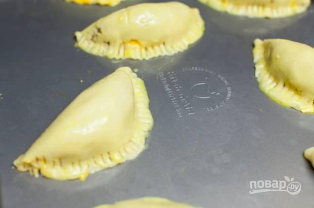 Духовку разогрейте до 200 градусов. Сформируйте пирожки, свернув тесто, как на фото и прижав края вилкой.