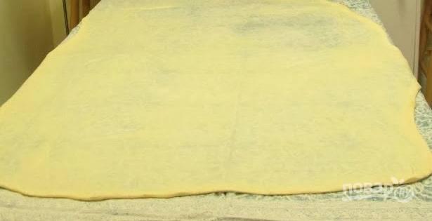 Разложите полотенце на стол, выложите тесто и аккуратно растяните его руками. Тесто должно быть очень тонким, прозрачным на вид.