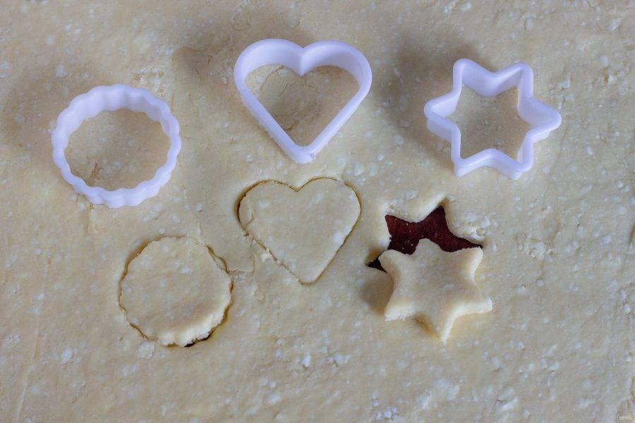 Достаем тесто из холодильника, раскатываем в пласт толщиной 0,5-0,7 см. и вырезаем формочками или стаканом печенье.