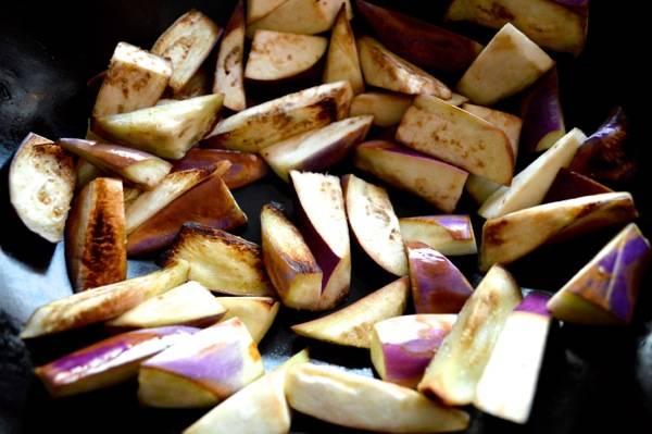 1. Сперва нужно сделать соус. Для его приготовления необходимо соединить кунжутное масло, соевый соус, сахар, рыбный соус и рисовое вино. Отставить соус в сторону. Тем временем нарезать небольшими ломтиками баклажаны и обжарить их на сковороде с растительным маслом.