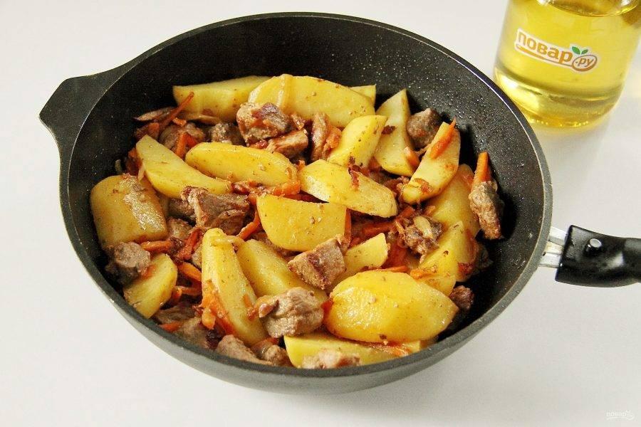 Добавьте крупно нарезанный картофель и обжарьте его до полуготовности.
