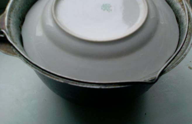 Кастрюлю накрываем тарелкой, предварительно залив подсоленной воды. Тушим на средней огне до готовности. Готовность проверяем опытным путем, то есть, просто попробовав толму на вкус. В среднем тушится 30-50 минут. Пока толма тушится, готовим чесночный соус со сметаной - выдавливаем чеснок в сметану и перемешиваем.