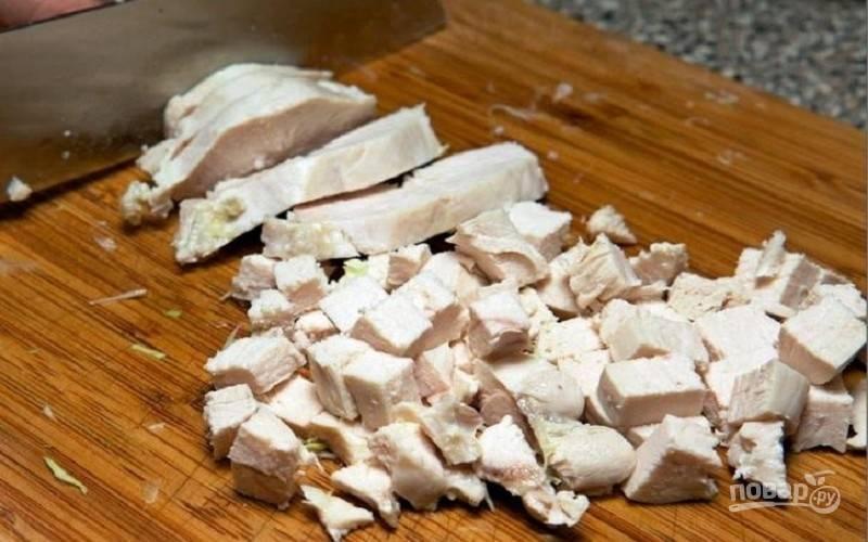 Вареное куриное филе нарежьте на кусочки, положите мясо в салатницу и смажьте этот первый слой майонезом или сметаной.