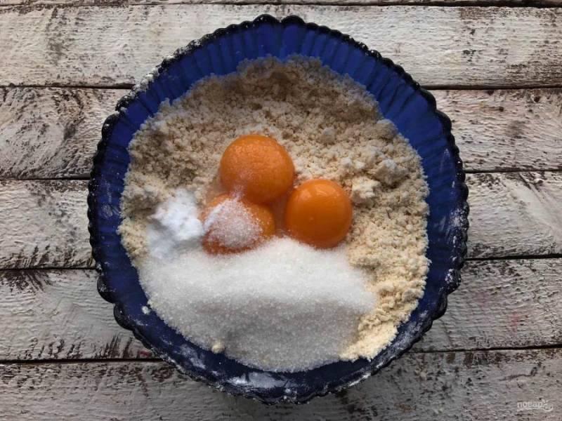 Белки отделите от желтков, белки отложите в сторону. К крошке добавьте желтки, сахар, ванилин и замесите тесто.