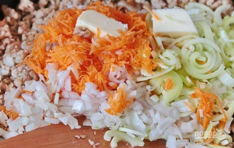 Очистите и вымойте порей и шалот. Нарубите оба вида лука вместе с чесноком. Добавьте овощи к фаршу и положите к ним двадцать грамм сливочного масла.