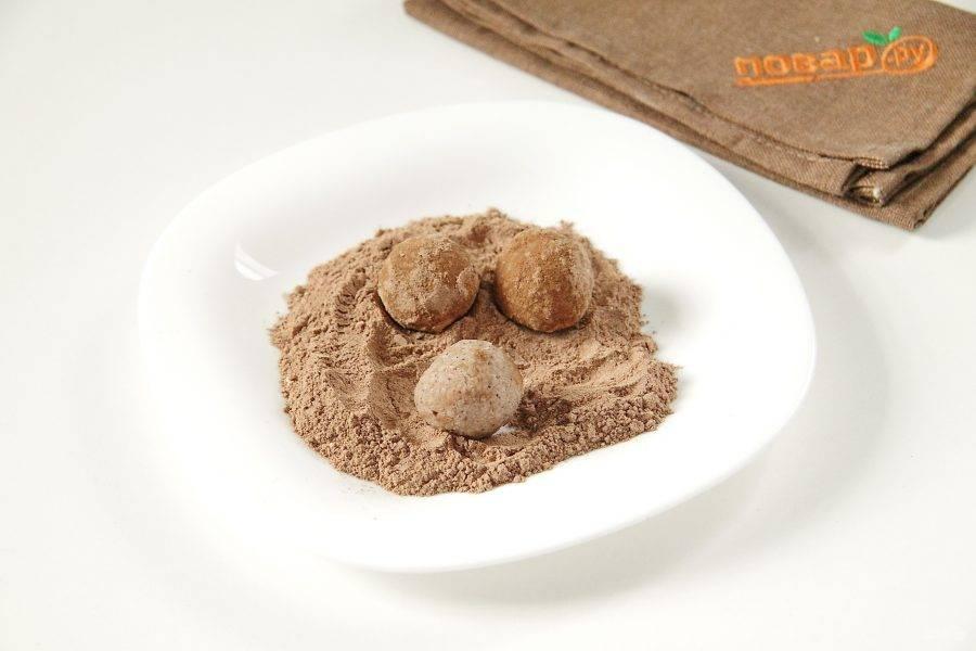 Скатайте из этой массы шарики, размером примерно чуть меньше грецкого ореха. Должно получиться примерно 17-20 штук. Соедините какао и сахарную пудру и обваляйте в этой смеси все конфеты.