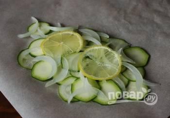 Возьмите четыре куска пергамента для запекания и выложите не него цуккини, затем — ломтики лука. Мелко порежьте масло, выложите его на овощи. Также положите сверху по несколько кружочков лимона.