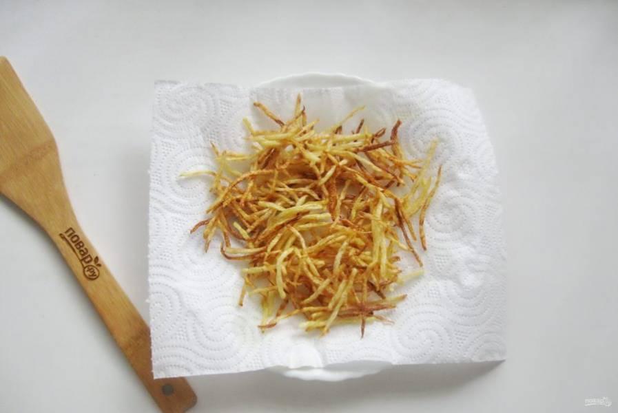 Подсолнечное масло налейте в посуду с толстым дном и хорошо накалите. Небольшими порциями обжаривайте картофель до золотистого цвета. Выложите на бумажное полотенце для удаления лишнего жира.