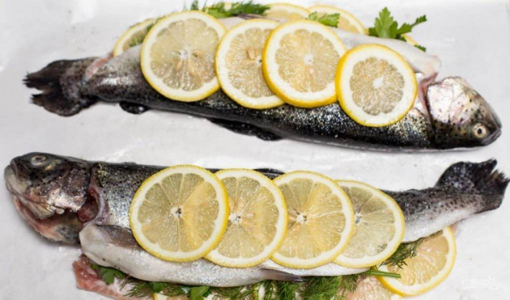 Форель закройте. Сверху сбрызните её маслом. Уложите дольки лимона. Переложите рыбу на пергамент в противне.