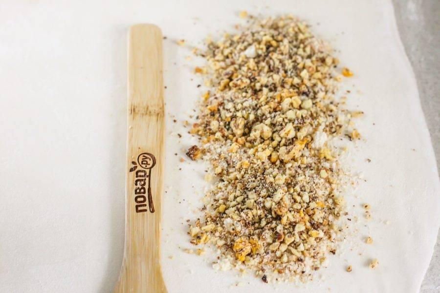 Слоеное тесто или тесто фило разморозьте, раскатайте его на рабочей поверхности в прямоугольный пласт. На узкие края пласта выложите измельченные сухари и ореховую крошку: ядер грецких орехов, фундука или арахиса.
