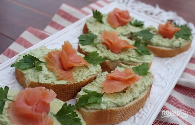 На кусочки багета намажьте пюре из авокадо. Сверху выложите лосося. Украсьте бутерброды петрушкой. Приятного аппетита!