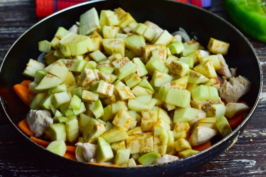 Баклажаны вымойте, очистите кожуру, нарежьте овощи кубиками. Выложите их к мясу.