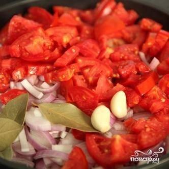 Затем добавляем в сковороду лук, чеснок, помидоры и лавровый лист.