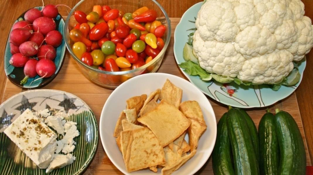 1. Овощи промойте. Помидорки разрежьте напополам, капусту разделите на маленькие соцветия и измельчите ножом, огурец нарежьте толстенькими полукольцами, редиску нарежьте кружочками. Приготовьте остальные ингредиенты. Я советую купить чипсы из питы или же обжарить нарезанную квадратиками питу на масле на среднем огне в сковороде до золотистого цвета.