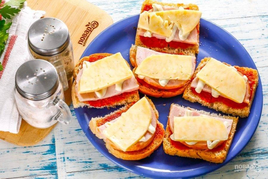 Твердый сыр нарежьте ломтиками и выложите на майонез. По желанию его можно измельчить на терке и выложить - таким образом он больше обволочет бутерброды.