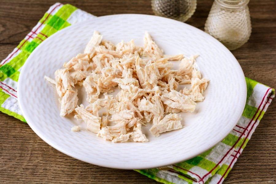 Отварите курицу в подсоленной воде в течение 20-25 минут, остудите и разделите руками на мелкие кусочки.