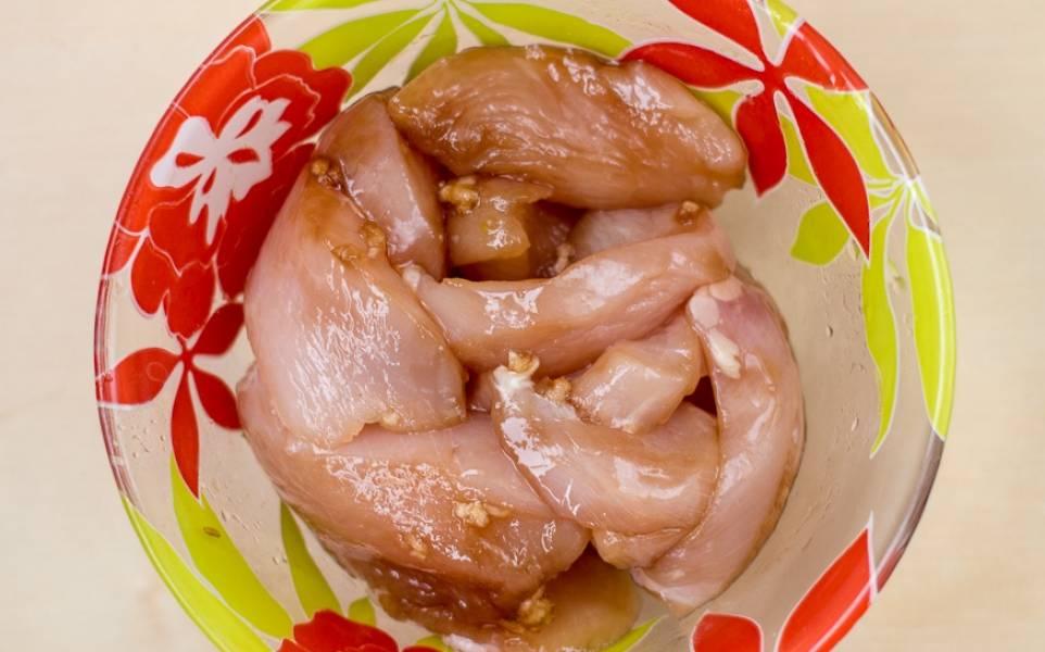 Грудку нарезаем небольшими кусочками, солим, выдавливаем чеснок и маринуем в соевом соусе в течение 20 минут.