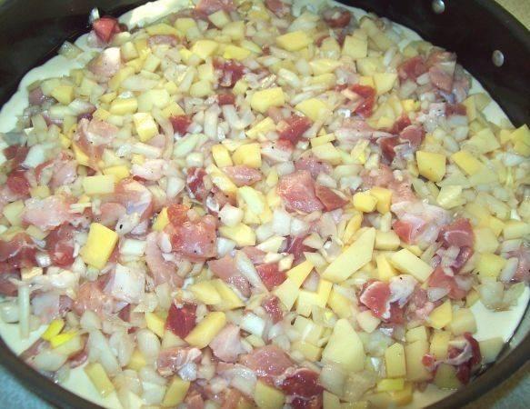 В смазанную маслом форму выливаем половину теста и равномерно выкладываем начинку.