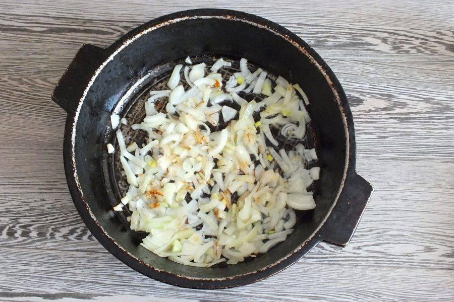 В жаровне разогрейте растительное масло и обжарьте до лёгкого румянца репчатый лук.
