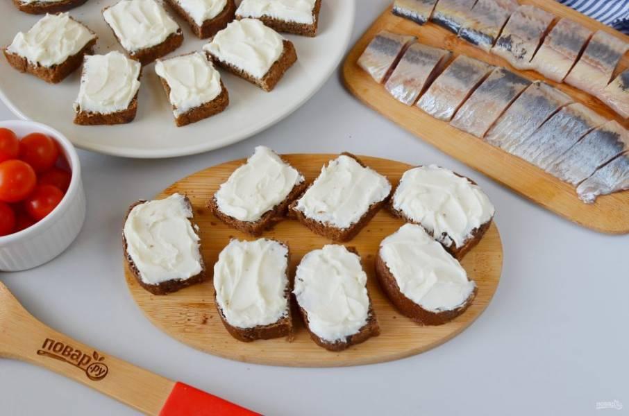 Черный хлеб порежьте пополам, каждую половинку смажьте щедро плавленым сыром.