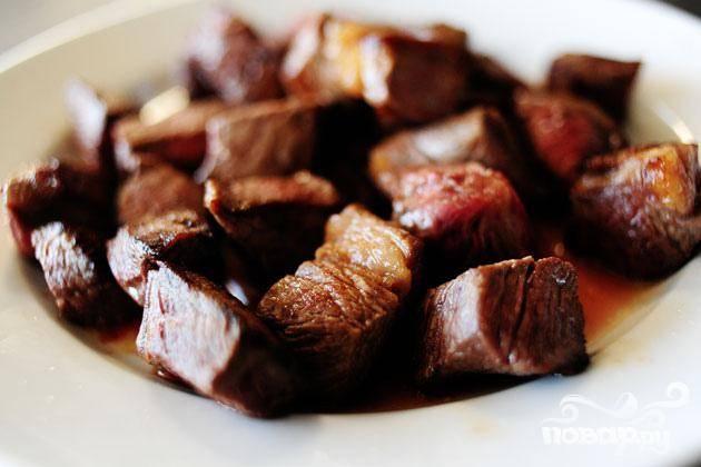 1. Нарезать луковицу кубиками. Очистить и крупно нарезать морковь. Разрезать картофель на 4 части. Пропустить чеснок через пресс. Нагреть оливковое масло и сливочное масло в большой кастрюле на среднем огне. Обжарить мясо в двух партиях. Выложить на тарелку, разрезать пополам и отложить в сторону.