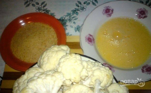 В небольшую пиалочку вбейте сырые куриные яйца. Взбейте их вилкой или венчиком, добавив соль и сахар. Капусту вымойте и разберите на соцветия.