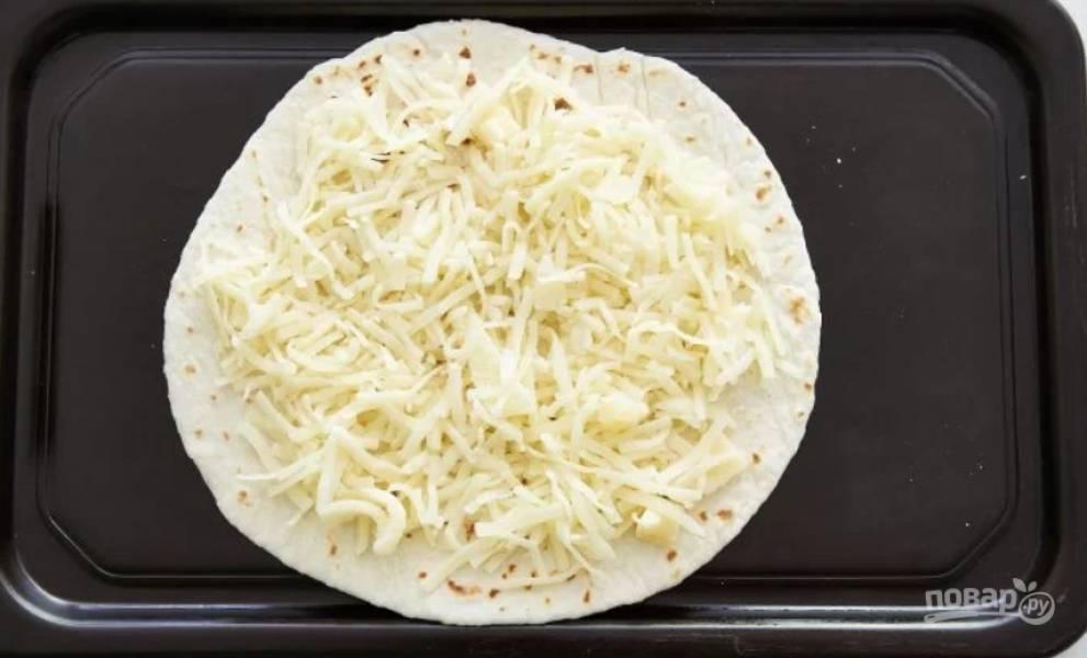 2.Выложите тортилью на противень, посыпьте немного сыром.