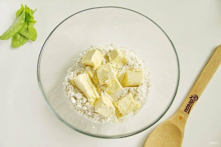 В глубокую миску насыпьте 1,5 стакана муки и добавьте нарезанное кубиками масло.