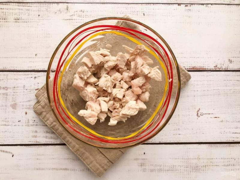Вареную куриную грудку нарежьте небольшими кусочками и выложите в глубокую тарелку.