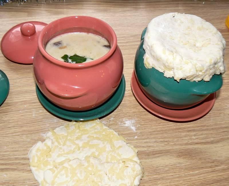 Разливаем горячий суп по горшочкам и накрываем их пластами теста. Я советую на горлышко горшочка перед этим положить деревянные палочки, потому что без них тесто может провалиться в горшочек при выпекании.
