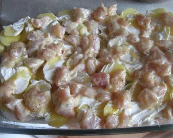 Картошку режем кружочками, сыр трем на терке. Смазываем форму для запекания маслом, выкладываем сначала лук, потом картошку и курицу.