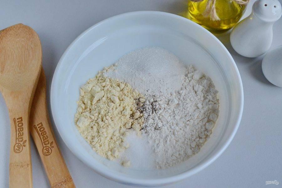 В глубокой посудине соедините кукурузную муку с пшеничной, сахаром, солью, разрыхлителем и перцем. Перемешайте.