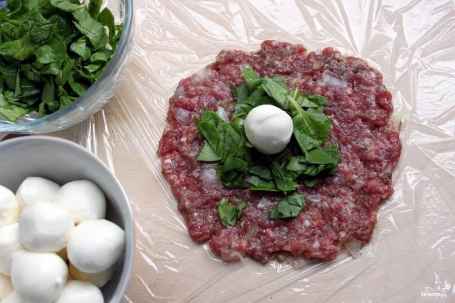 4.Каждую часть руками выложите на пищевую пленку, оформите в виде круга, сверху положите порезанные листья шпината и небольшую моцареллу.
