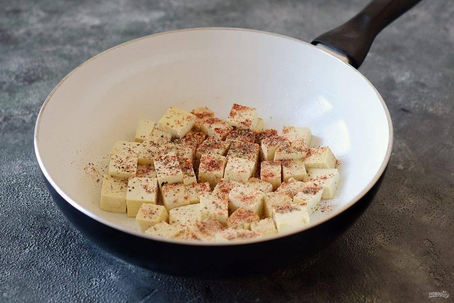 Тофу нарежьте кубиками. Обжарьте на сковороде со специями до румяной корочки, постоянно помешивая. Затем отложите в сторону.