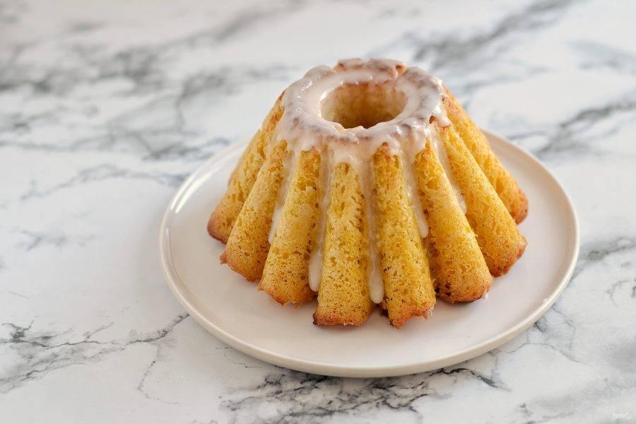 Разогрейте духовку до 180 градусов и выпекайте 30 минут. Остудите, вытащите из формы. Для глазури смешайте лимонный сок и сахарную пудру. Покройте им кекс.