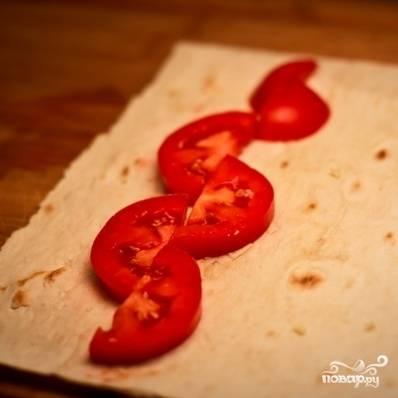 На край лаваша выкладываем кусочки помидора.