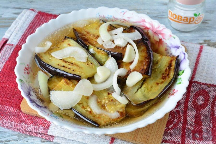 Выкладывайте баклажаны слоями, пересыпая луком и чесноком. В конце залейте остывшим маринадом. Поставьте закуску в холодильник на 5-6 часов, чтобы баклажаны промариновались.