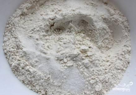 В миску просеиваем муку, добавляем сахар (обычный и ванильный), соль, сухие дрожжи. Перемешиваем.
