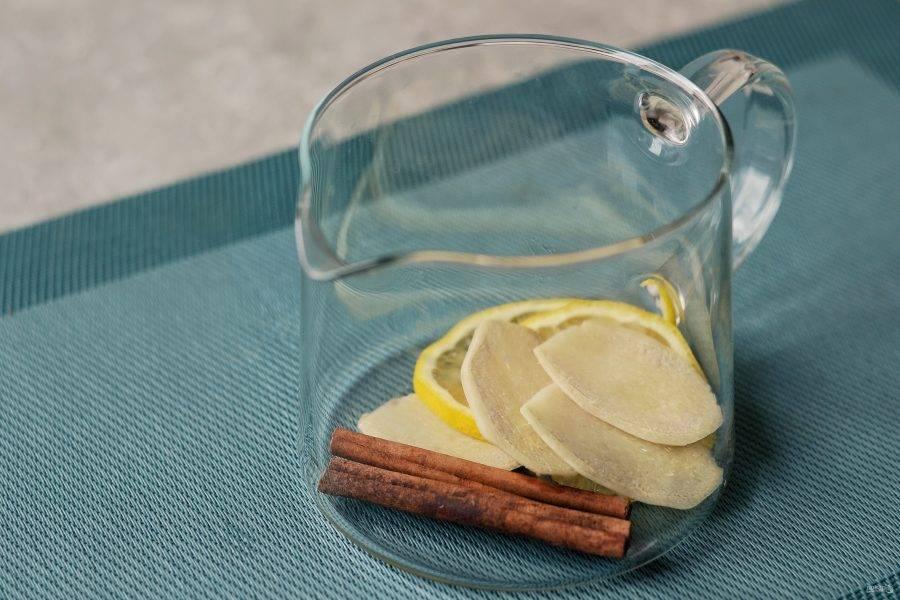 Переложите лимон, имбирь и палочку корицы в заварочный чайник.